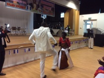 Sir Matthias Walukaga the chief entertainer dancing with a fan.