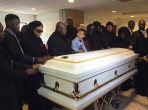 Sarah Amin's children around her casket